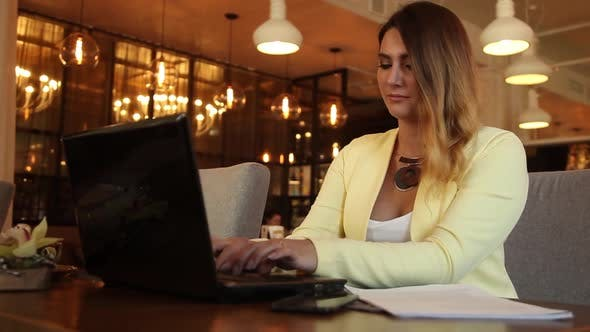 Business Woman in Business Clothes Working with Documents Using a Mobile Computer