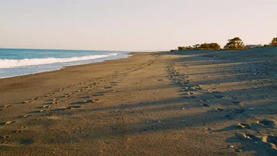 Footprints on the sandy beach at sunset