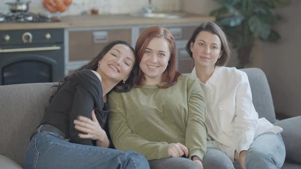 Thumbnail for Friendly Young Women Sitting on Couch Looking at Camera and Smiling