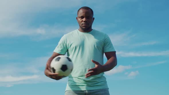 Thumbnail for Determined Black Man Holding Soccer Ball in Park