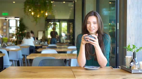 Cover Image for Young Woman Calling with Cell Telephone While Sitting Alone in Coffee Shop During Free Time