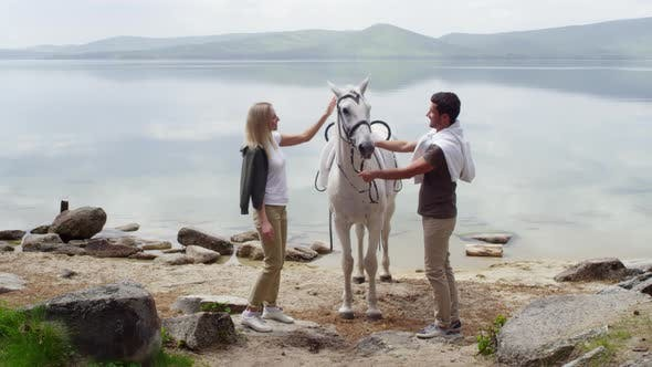 Thumbnail for Couple Petting White Horse by the Lake