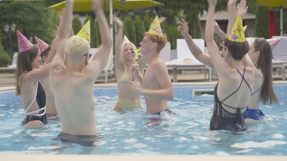 Thumbnail for Happy Young People in Party Hats Dancing Around Redhead Man in Pool on Sunny Day Outdoors. Group of