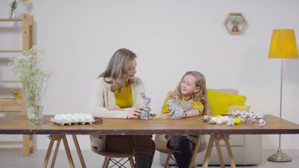 Thumbnail for Frau und Mädchen spielen mit Osterhase Figuren