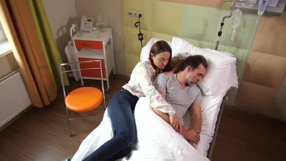 Thumbnail for Upset Wife Lying on Bed Near Sick Sleeping Husband