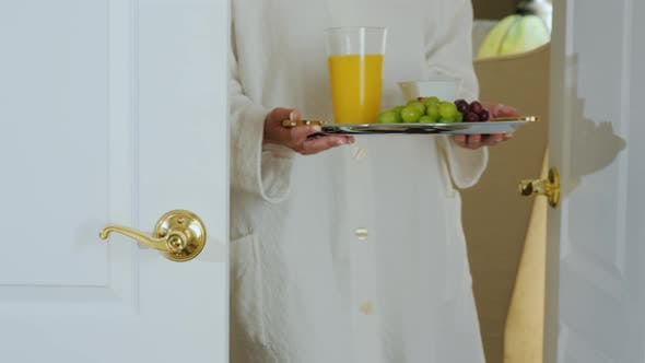 A Woman in a Bathrobe Brings Breakfast To the Room