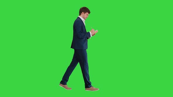 Thumbnail for Thinking Businessman Writing Notes in His Notebook While Walking on a Green Screen, Chroma Key
