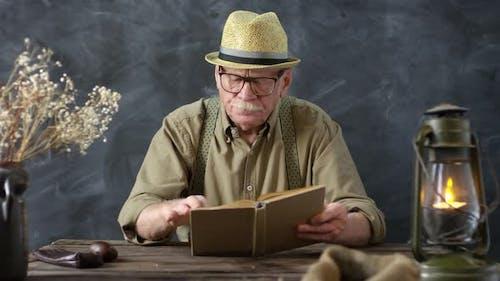 Old-Fashioned Senior Man Reading Book