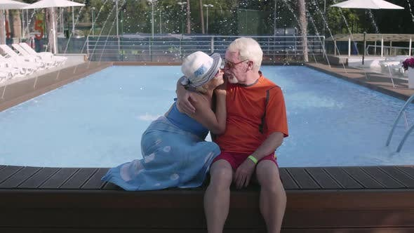 Thumbnail for Happy Mature Couple Sitting on the Edge of the Pool