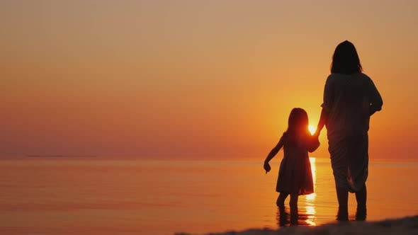Thumbnail for A Pregnant Woman with a Daughter Is Standing on the Beach at Sunset. Waiting for the Second Child