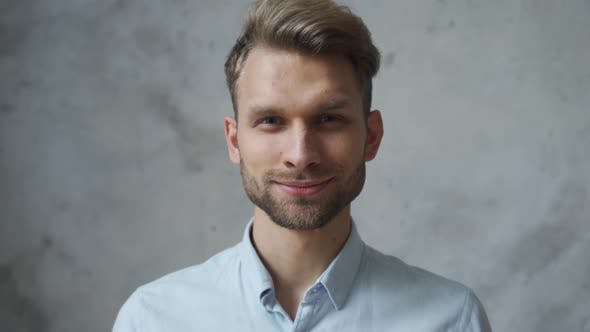 Confident Smiling Young Business Man Looking at Camera at Grey Wall Portrait