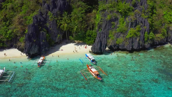 Cover Image for Tourists Enjoy Azure Sea and Tropical Island on the Entalula Beach in El Nido, Palawan, Philippines.