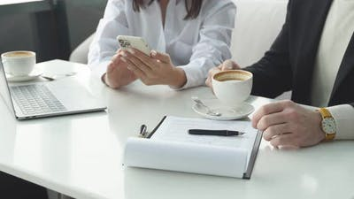 Business Lady Uses a Smartphone at a Business Meeting with a Man a Business Colleague an Image