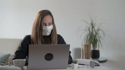 Young woman freelancer with mask using laptop computer and  typing message