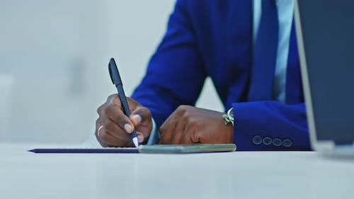 Closeup of a Black Businessman's Hand with a Pen Signs Papers