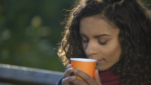 Cover Image for Young Curly-Haired Woman Enjoying Taste of Favorite Morning Coffee Outdoors