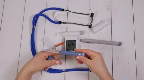 A Diabetic Woman Dials the Right Dose of Insulin on an Insulin Pen