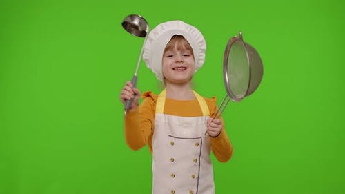Funny Child Girl Cook Chef Baker in Apron and Hat Dancing with Sieve and Ladle Fooling Around
