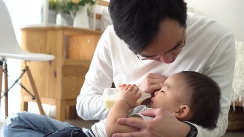 Asian Family of Young Father Feeding a Baby Boy From Milk Bottle