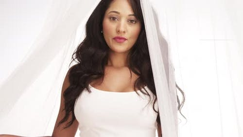Beautiful Mexican woman standing behind curtain