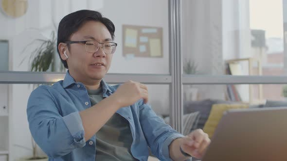Thumbnail for Asian Office Worker Typing on Laptop and Falling Asleep at Desk