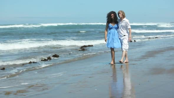Thumbnail for Couple walking together along beach