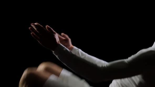 Cover Image for Beautiful Male Gymnast in White Doing Acrobatic Stunts on Black Background in Slow Motion, Rotation