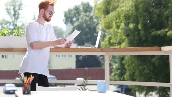 Thumbnail for Young Designer Reading Documents, Standing in Balcony Outdoor