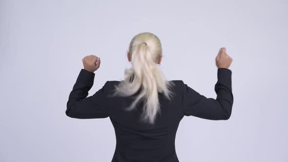 Cover Image for Rear View of Young Happy Blonde Businesswoman with Fists Raised