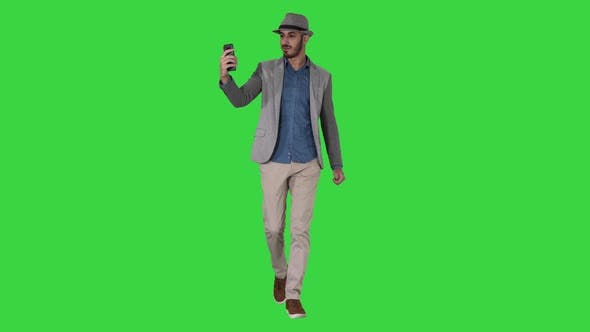 Thumbnail for Attractive Man in Casual Clothes Hat Hipster Stylerecording Vlog or Making a Video Call on a Green