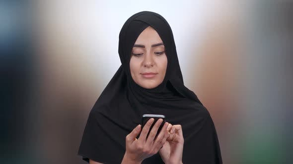 Portrait of a Young Muslim Woman, a Female in a Hijab Communicates and Uses Smartphone on a Blurred
