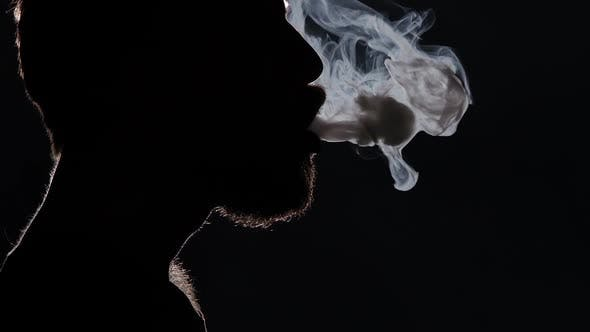 Thumbnail for Man Smoking a E-cigarette and Coughing. Black. Silhouette. Close Up
