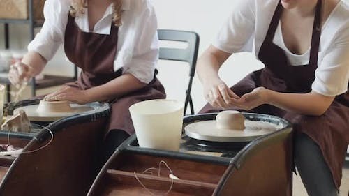 Two Female Ceramic Artists in Apron Using Clay Material Working in Potter Studio. Evening Freelance