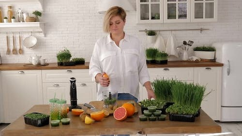 A Young Woman Prepares a Cocktail with Orange Juice and Microgreens