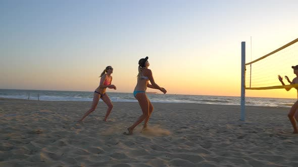 Thumbnail for Women players play beach volleyball and celebrate a point won.