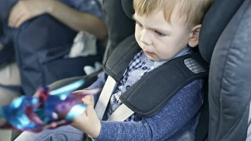 Child Playing with Windmill Toy in Car Seat