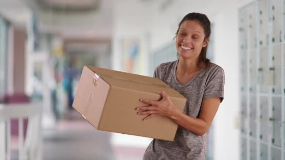 Thumbnail for Cheerful young woman at post office tossing box into air excited to open it