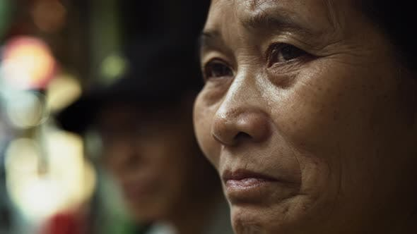 Thumbnail for Handheld view of Vietnamese senior woman in the street. Shot with RED helium camera in 8K