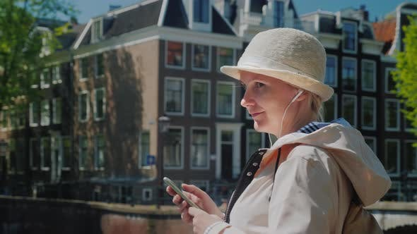 Thumbnail for Stylish Woman with a Smartphone Stands on the Canal in Amsterdam on the Background of Old Houses