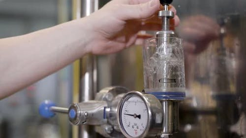 Close-up Shot of a Brewer Turning Tube Lever in a Brewery Factory