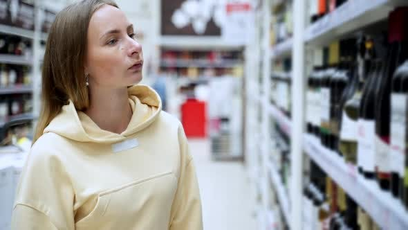 Thumbnail for Woman Chooses Wine in the Supermarket, Customer Selects Product on the Shelves in the Store