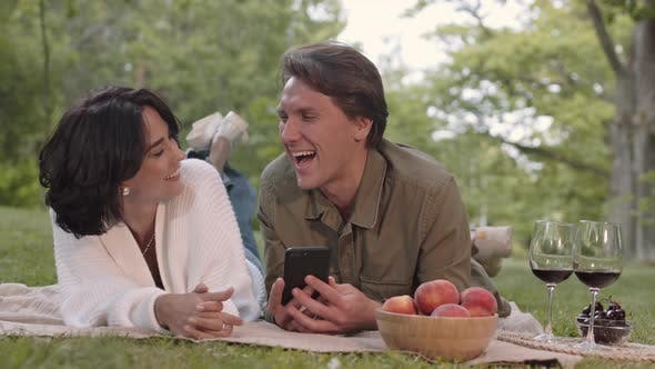 Thumbnail for Happy Couple Using Telephone on Picnic