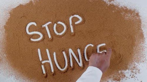 Hand Writes On Soil  Stop Hunger