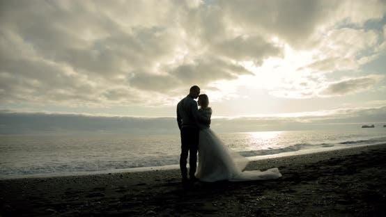 Thumbnail for Küssendes Hochzeitspaar steht gegen den Sonnenuntergang an einem Strand in Island.