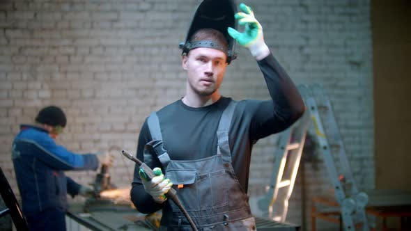 Thumbnail for Young Handsome Man Standing in the Workshop Holding a Welding Instrument