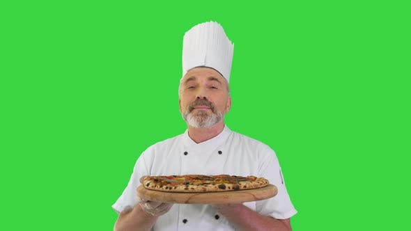 Smiling Chef Smelling Delicious Pizza and Doing Real Jam Gesture on a Green Screen, Chroma Key.