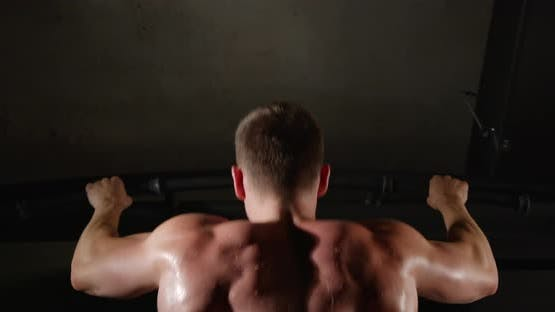 A man with beautiful muscles on his back, in the gym, pulls himself up on a horizontal bar