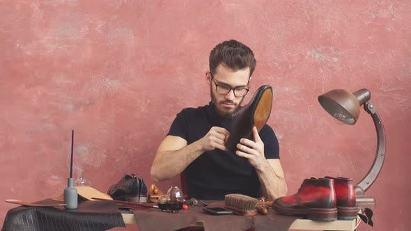Thumbnail for Young Man Checking the Glued Sole Beautiful Repaired Shoes in Man's Hands