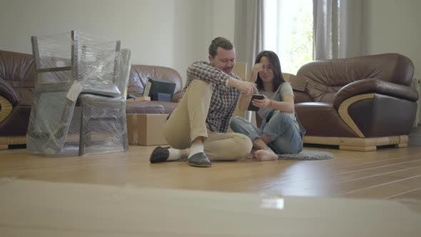 Cover Image for Happy Caucasian Family Sitting on the Floor in Living Room with New Furniture and Using Smart Phone