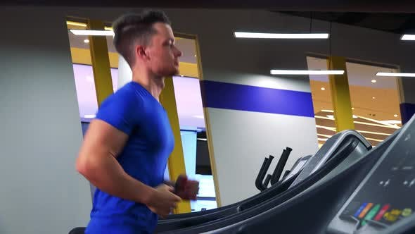Thumbnail for A Young Fit Man Jogs on a Treadmill in a Gym - View From Side